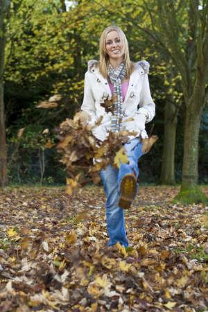 blonde yeux bleus: Une belle blonde aux yeux bleus cheveux jeune femme marche dans une for�t en s'amusant � voix haute les feuilles d'automne Banque d'images