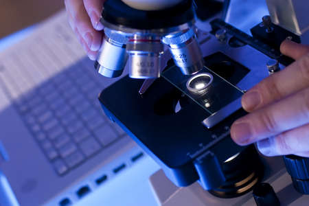 clinical laboratory: A medical or scientific researcher using a microscope and laptop