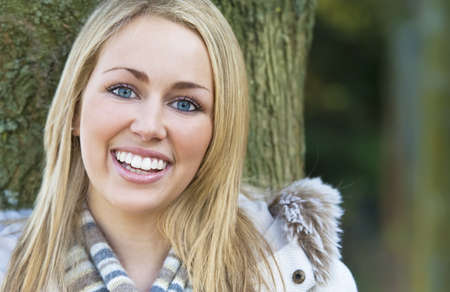 A beautiful blond haired blue eyed model with a beautiful smile shot in woodland surroundings using natural light. Stock Photo - 4366901