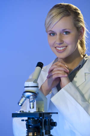 Un hermoso mujeres m�dicos o cient�ficos investigador utilizando su microscopio. Foto de archivo - 4366895