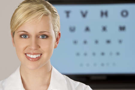 eye test: A beautiful female optician shot with an electronic eye test chart out of focus behind her.  Stock Photo