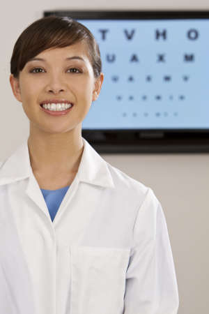 A beautiful female optician shot with an electronic eye test chart out of focus behind her. Stock Photo - 4413123