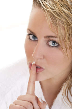 Studio shot of a beautiful blond haired blue eyed female model holding her finger up to her lips Stock Photo - 4413127