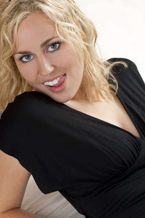 blonde yeux bleus: Une belle chevelure blonde aux yeux bleus, portant sexy jeune femme sur son lit et � l�cher ses dents Banque d'images