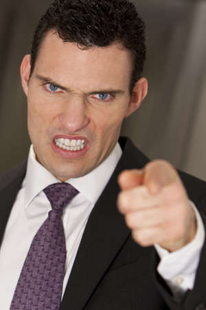 reacting: Close up studio shot of a smartly dressed man reacting angrily to camera