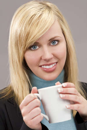 a beautiful young blond woman smartly dressed and drinking a mug of tea or coffee photo