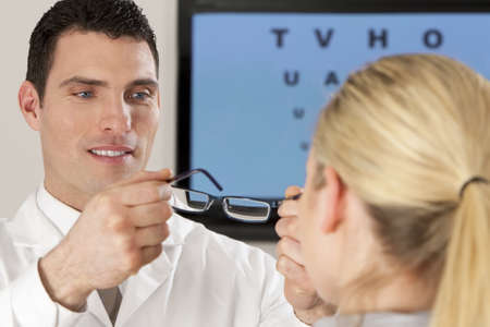 A male optician fitting glasses onto a blond female patient with an electronic eyechart out of focus behind him.