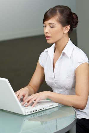A beautiful young oriental woman using a laptop in a modern office photo