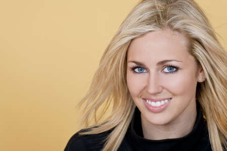 Studio shot of a beautiful young blond woman with bright blue eyes looking happy Stock Photo - 4522398
