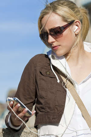 A beautiful young blond woman outside listening to music on her MP3 player Stock Photo - 4543857