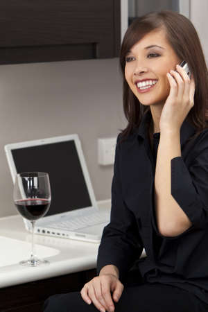 A beautiful young oriental woman with a wonderful toothy smile drinking red wine, chatting on her cell phone and using a laptop in her kitchen. Stock Photo - 4561676