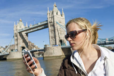 british girl: A beautiful young blond woman listening to music on her MP3 player next to the famous Tower Bridge in London, England
