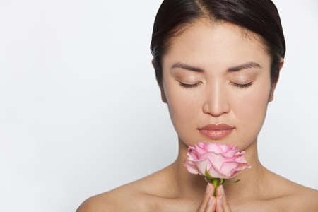 meditation woman: Studio shot of a beautiful young Japanese woman holding a pink rose between her clasped hands while in meditative contemplation