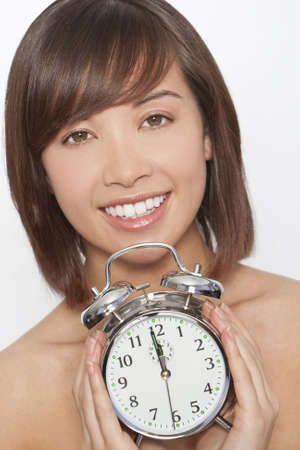 A naturally beautiful oriental woman make up free and holding an alarm clock just about to get to 12 oclock photo