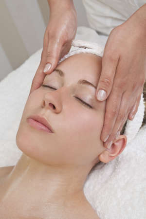 A young woman relaxing at a health spa while having a massage Stock Photo - 4601340