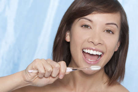 A naturally beautiful young woman make up free, brushing her teeth and smiling