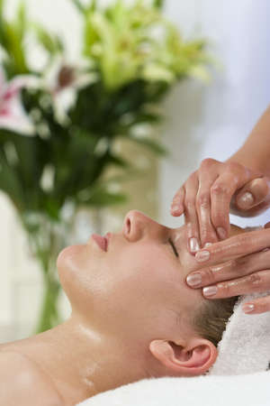 facial massage: A young woman relaxing at a health spa while having a massage