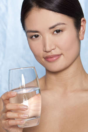 Studio shot of a beautiful young Japanese woman drinking a glass of mineral water photo