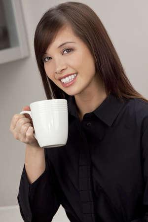 dentudo: Una joven y bella mujer oriental con una maravillosa sonrisa Toothy beber de una taza blanca Foto de archivo