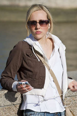 A beautiful young blond woman outside listening to music on her MP3 player Stock Photo - 4641813