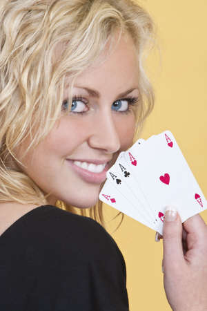 A beautiful young woman holding a hand of four aces showing them to the camera and looking happy.
