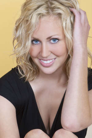 Studio shot of a beautiful blond haired blue eyed female model looking happy Stock Photo - 4753926