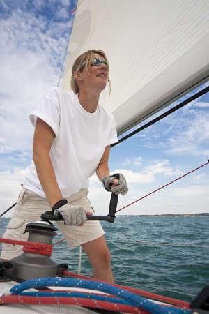 Plan de la belle jeune femme sur le pont d'un bateau de l'exploitation d'un treuil pour hisser une voile