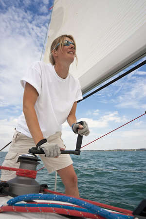 boat crew: Shot of beautiful young woman on the deck of a boat operating a winch to hoist a sail