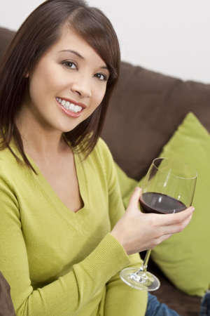A beautiful young oriental woman with a wonderful toothy smile drinking redwine at home on her settee. Stock Photo - 4753930