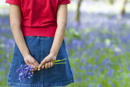 Shot of a little girl holding a bunch of blue bells behind her back, shot against an out of focus background of a bluebell wood. Stock Photo