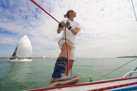 Szeroki kąt strzału pięknych młoda kobieta na pokładzie łodzi posiadania lina natomiast za jej jacht jest jej łódź jest ona wyścigowych przeciw. Zdjęcie Seryjne