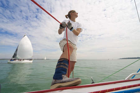 Wide angle shot of beautiful young woman on the deck of a boat holding a rope while behind her a yacht her is a boat she is racing against.