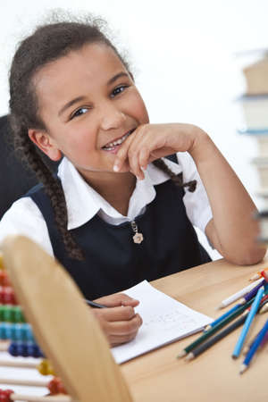 A beautiful young mixed race girl writing in a school classroom surrounded by books and an abacus