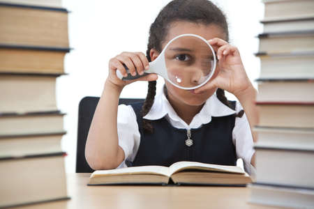 A beautiful young mixed race girl looking through a magnifying glass while reading in a school classroom with two piles of books in front of her. photo
