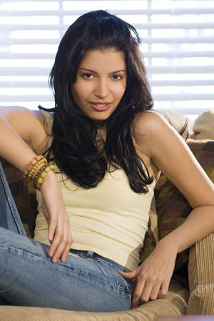settee: A beautiful young hispanic woman relaxing on a settee at home.