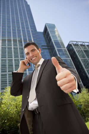 A young male executive in a city surrounding talks on his cell phone and gives a thumbs up photo