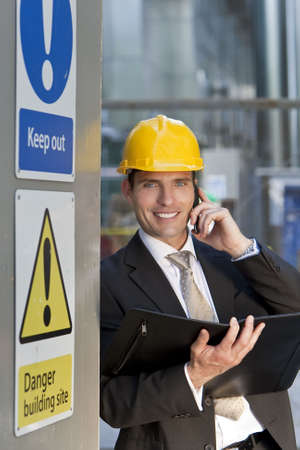 A male manager on a construction site wearing a hard hat and talking on his phone