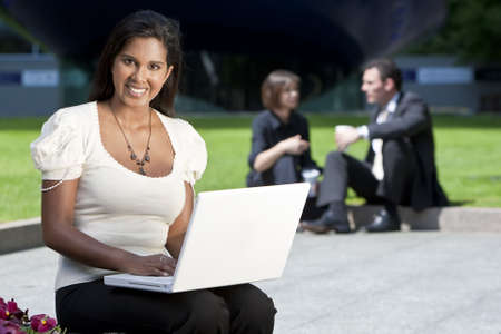 A beautiful young Asian woman using her laptop outside while behind her out of focus are an executive couple sitting having coffee Stock Photo - 4918652