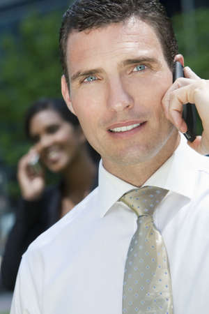 A young male executive talking on his cell phone with his female colleague on her phone out of focus in the background Stock Photo - 4927385