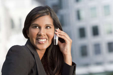 A beautiful young Asian businesswoman with a wonderful smile chatting on her cell phone with an out of focus city scene behind her. Stock Photo - 4927386