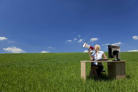 location shot: Business concept shot of a beautiful young woman sitting at a desk using a megaphone in a green field with a bright blue sky. Shot on location. Stock Photo