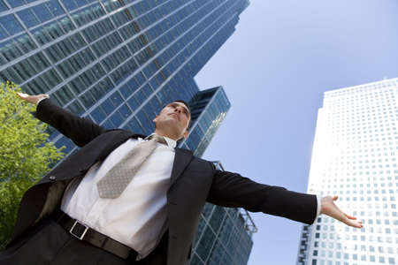 messiah: A businessman with his arms out stretched messiah like in a modern city environment with the glass fronted office buldings reflecting the sun behind him Stock Photo
