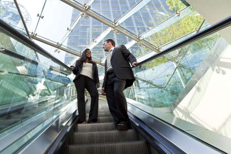 corporate buildings: A young male and female executive ride an escalator together in a modern hi-tech city setting Stock Photo