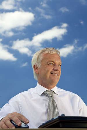 Business concept shot showing an older male executive using a computer with a blue sky complete with fluffy white clouds. Shot on location not in a studio. photo