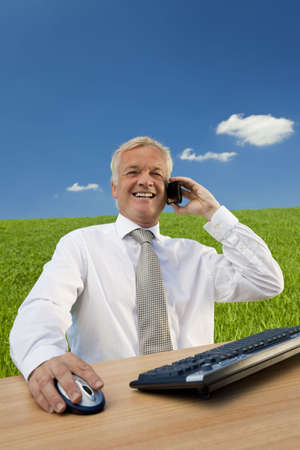 Business concept shot showing an older male executive sitting at a desk, using his computer and talking on his cell phone in a green field with a blue sky complete with fluffy white clouds. Shot on location not in a studio. photo