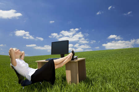 Business concept shot of a beautiful young woman relaxing at a desk in a green field with a bright blue sky. Shot on location. Stock Photo - 4956235