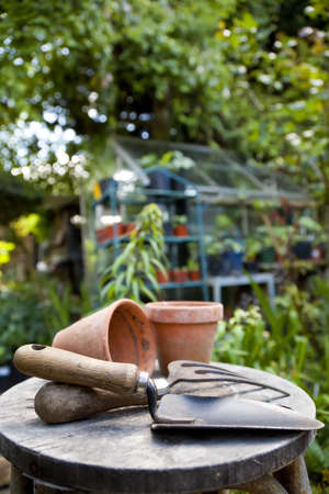 Gardening utensils and flowere pots resting on a stool in a green garden with a greenhouse out of focus in the background