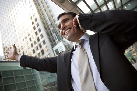A young male executive celebrating success on his cell phone in front of a high rise office block in a modern city photo