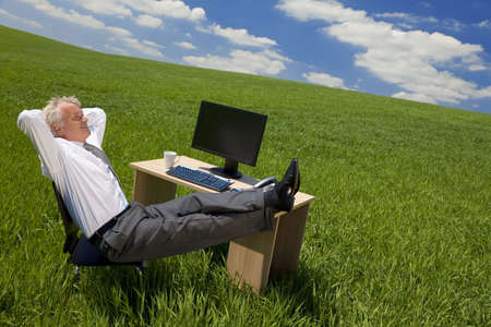 Business concept shot of a businessman relaxing with his feet up on his desk in a green field with a bright blue sky full of fluffy white clouds. Shot on location. photo