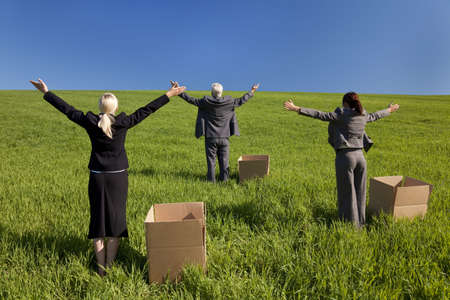 Concept shot showing three business executives, one male and two female standing outside boxes in a green field and raising their arms towards the horizon. Environmental and business concepts, shot on location. photo